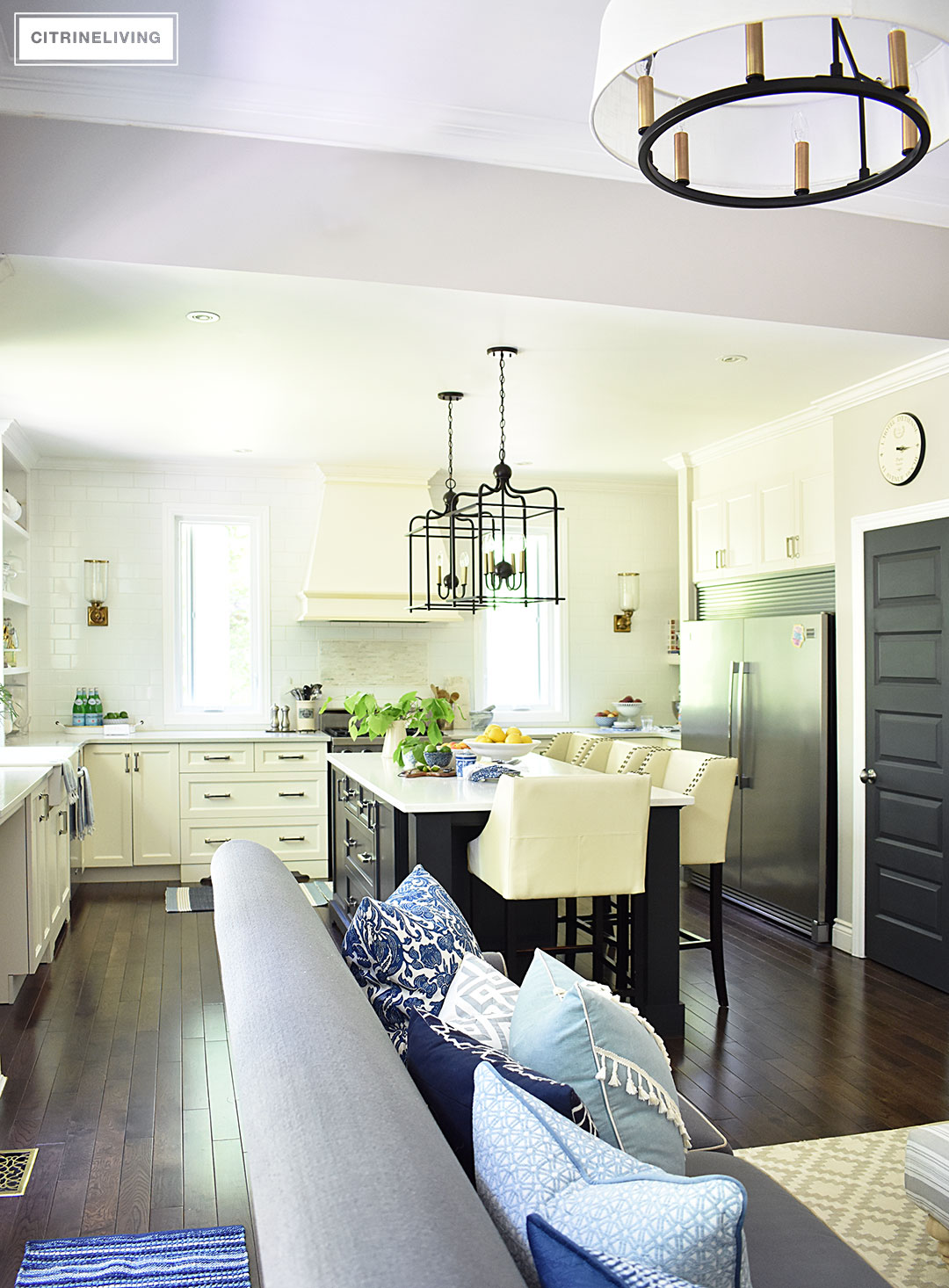 White kitchen with black island decorated for Summer with fresh cute greenery and bowls filled with bright, seasonal fresh fruit for a vibrant punch of seasonal color. Blue and white dishes and bowls are a classic touch.