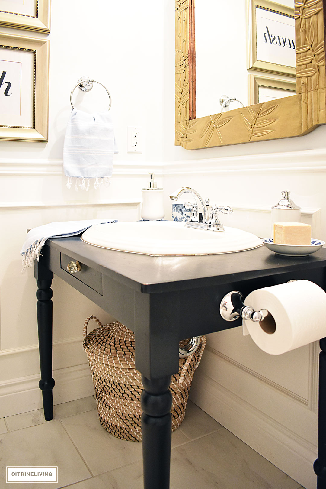Small bathroom with white wainscotting, light blue walls, black vanity and gold accents.