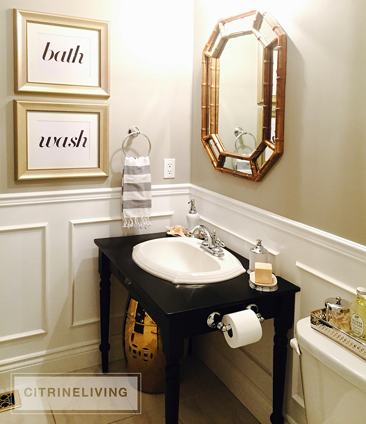 Small bathroom with black vanity and gold vintage bamboo mirror.