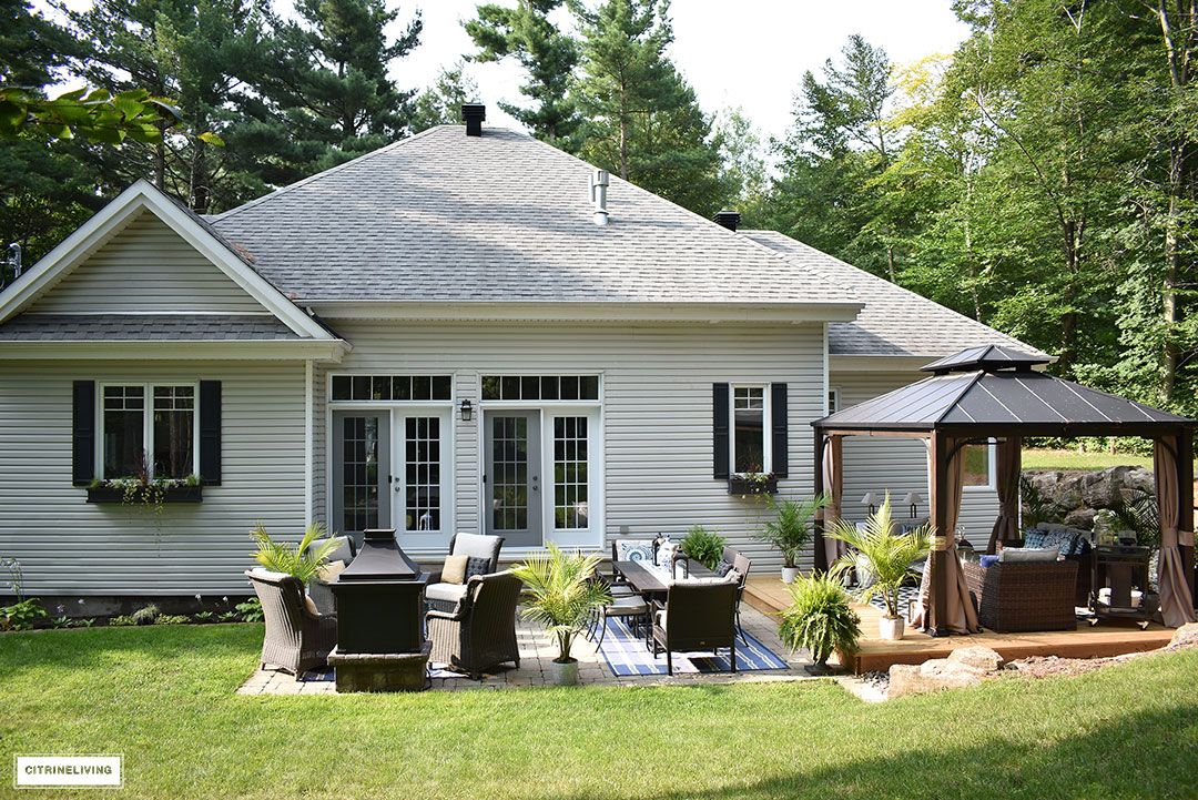 Home Exterior With Grey Siding And Roof, Black Shutters And Window Boxes,  And Backyard