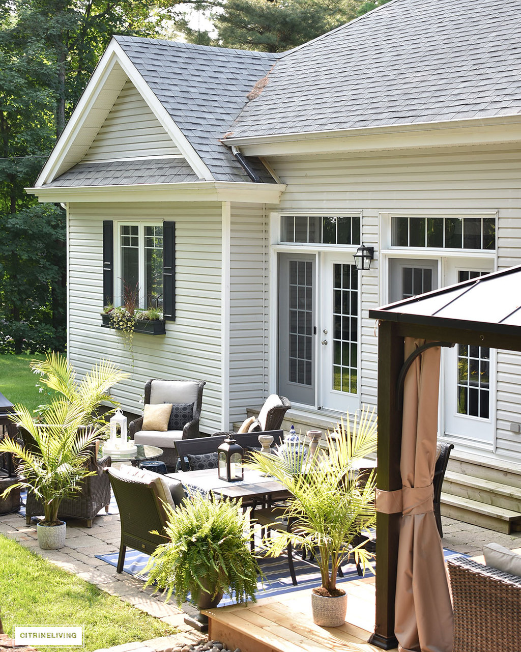 Home exterior with grey siding and roof, black shutters and window boxes, and backyard patio featuring 3 entertaining zones - lounge, dining and conversation.