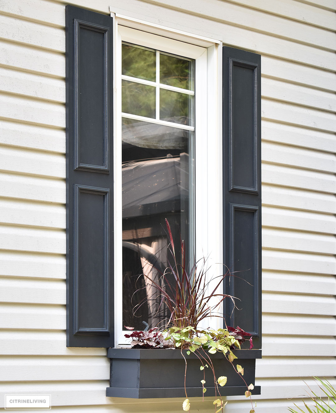 DIY black shutters and window boxes add character to this window.
