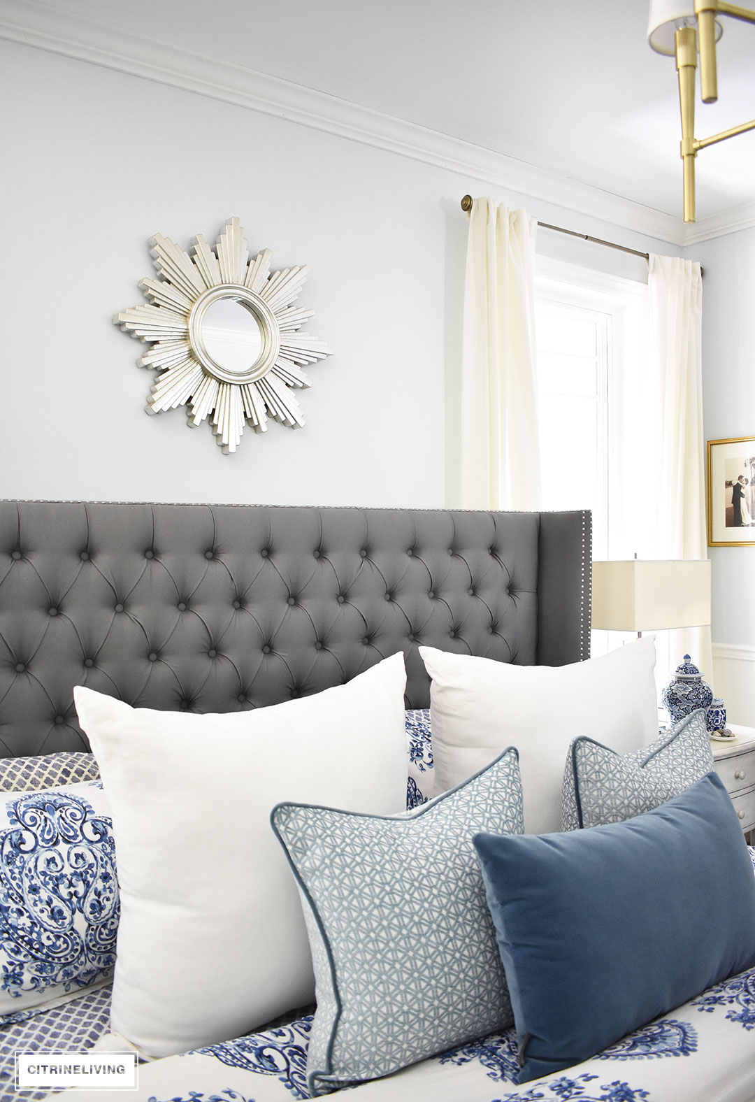 A sunburst mirror is a chic and classic addition to any space! This beautiful blue and white bedroom accented with a mix of cool and warm metals is elegant, warm and inviting. A metallic sunburst mirror as the perfect finishing touch.