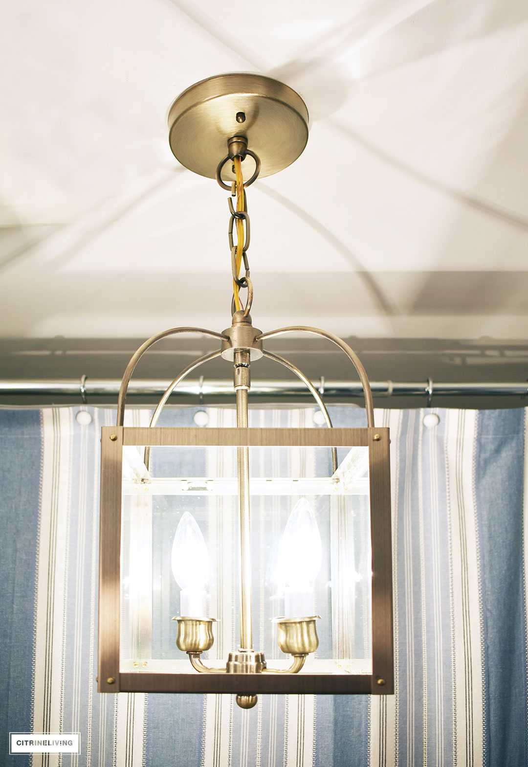 A timeless blue and white bathroom makeover featuring grasscloth, brass lighting, a blue and white striped shower curtain and blue and white accessories creates a sophisticated and elegant look in this small bath.