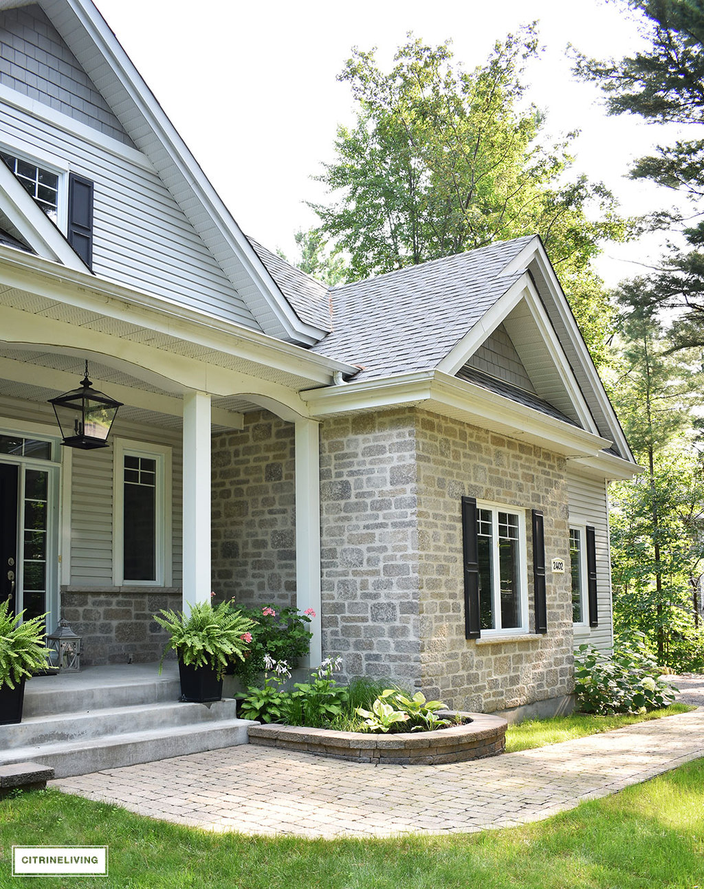East coast style home featuring overscale black pendant porch light - Crestwood pendant by Progress Lighting - black front door, black shutters and two-tone grey siding and stone.