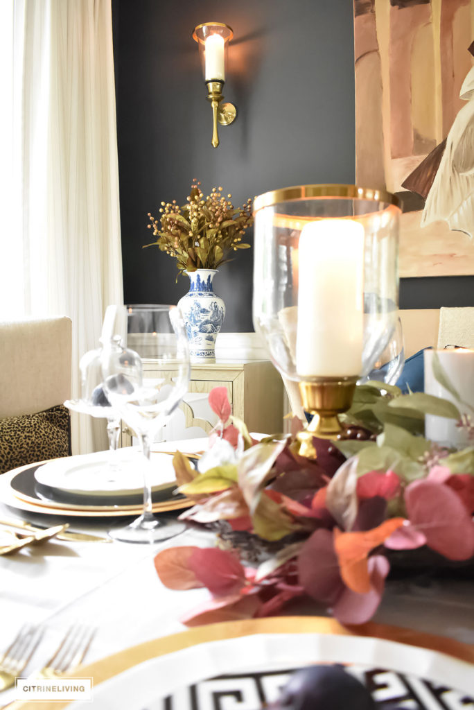 Fall tablescape with brass hurricanes, blue and white vases and faux foliage in rich autumn colors. Brass wall sconce.
