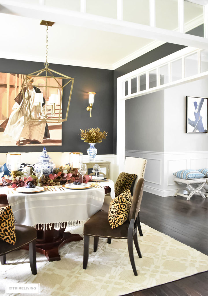 Fall Home Tour. Black dining room with elegant furniture. Leopard pillows. Brass overscale lantern style chandelier. Blue and white accents.