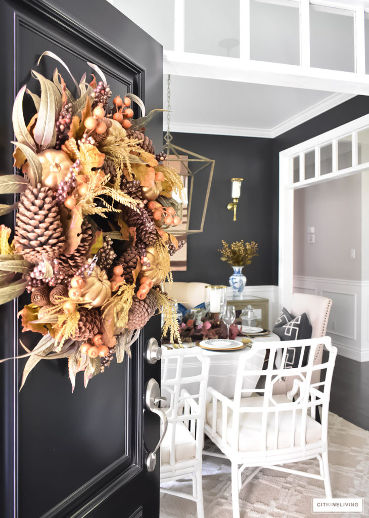 Beautiful Fall wreath with rich burgundy, orange and gold details adorns this traditional black front door.