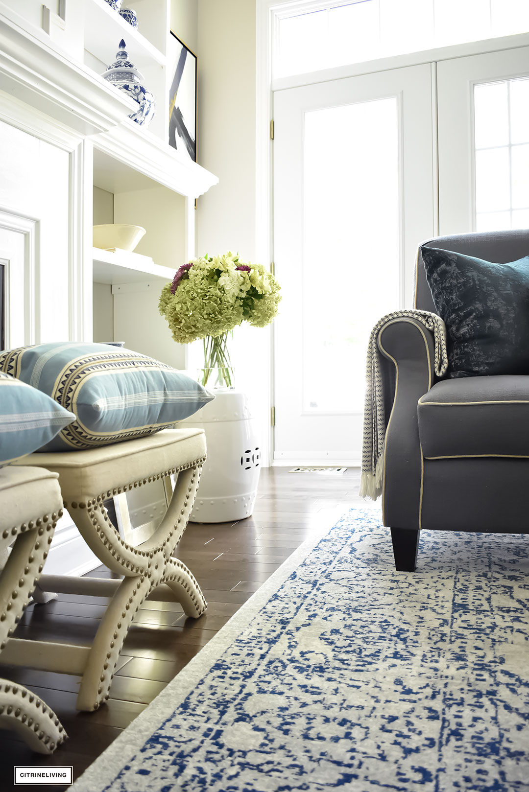 Fal Home Tour. Living room with upholstered stools, blue vintage rug, blue and white accents and pillows.