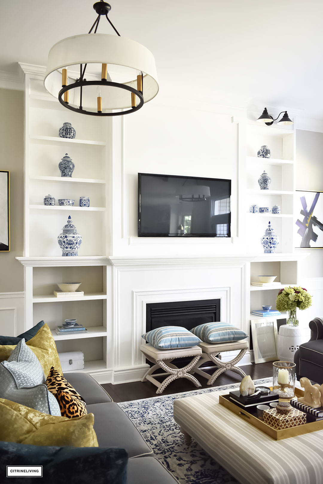 Fall Home Tour featuring this elegant living room with sophisticated navy and gold accents, drum shade chandeliers, gray sofas and blue and white accessories. Blue vintage style rug. Built in bookshelves.