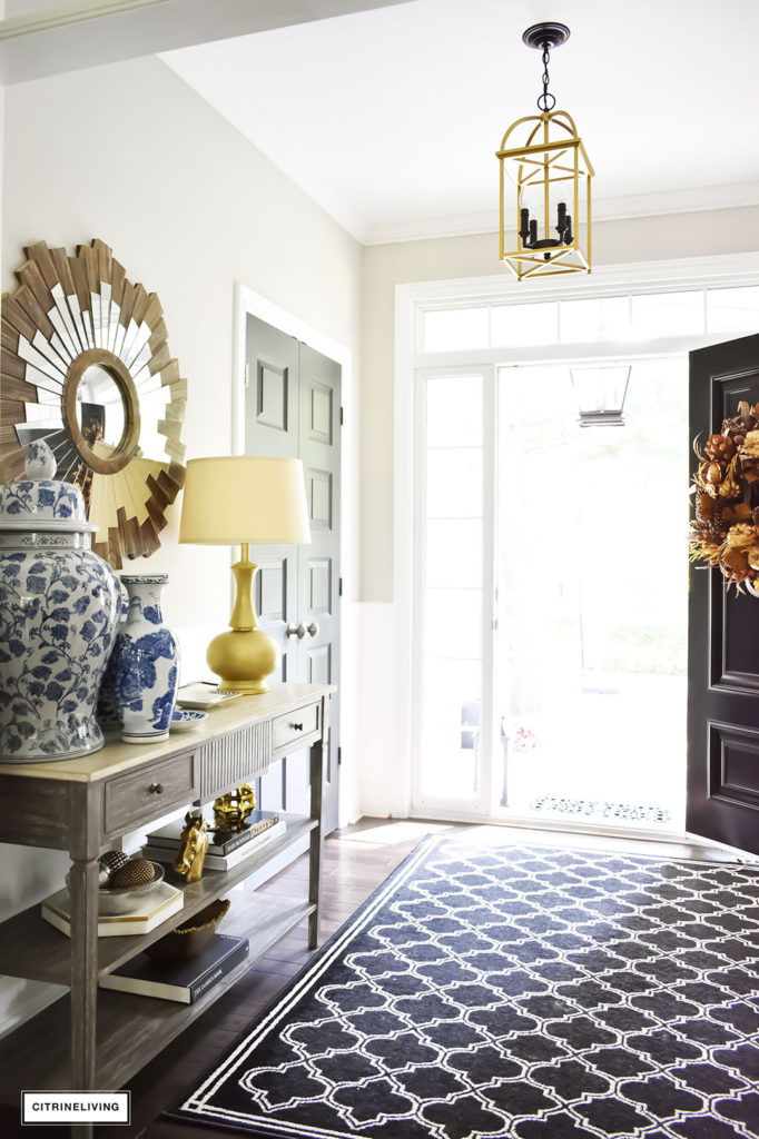 Fall home tour with elegant entryway featuring layers of gold accessories and blue and white ginger jars. Black and white quatrefoil rug. Two-toned brass and black pendant light
