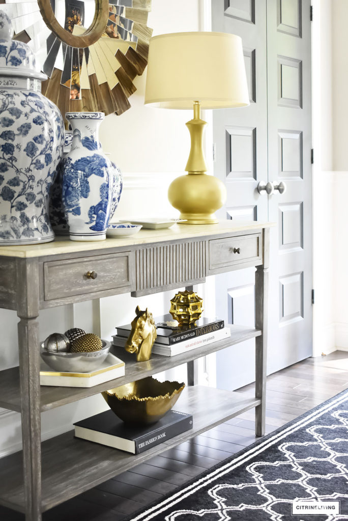 Fall home tour with elegant entryway featuring console table with layers of gold accessories and blue and white ginger jars.
