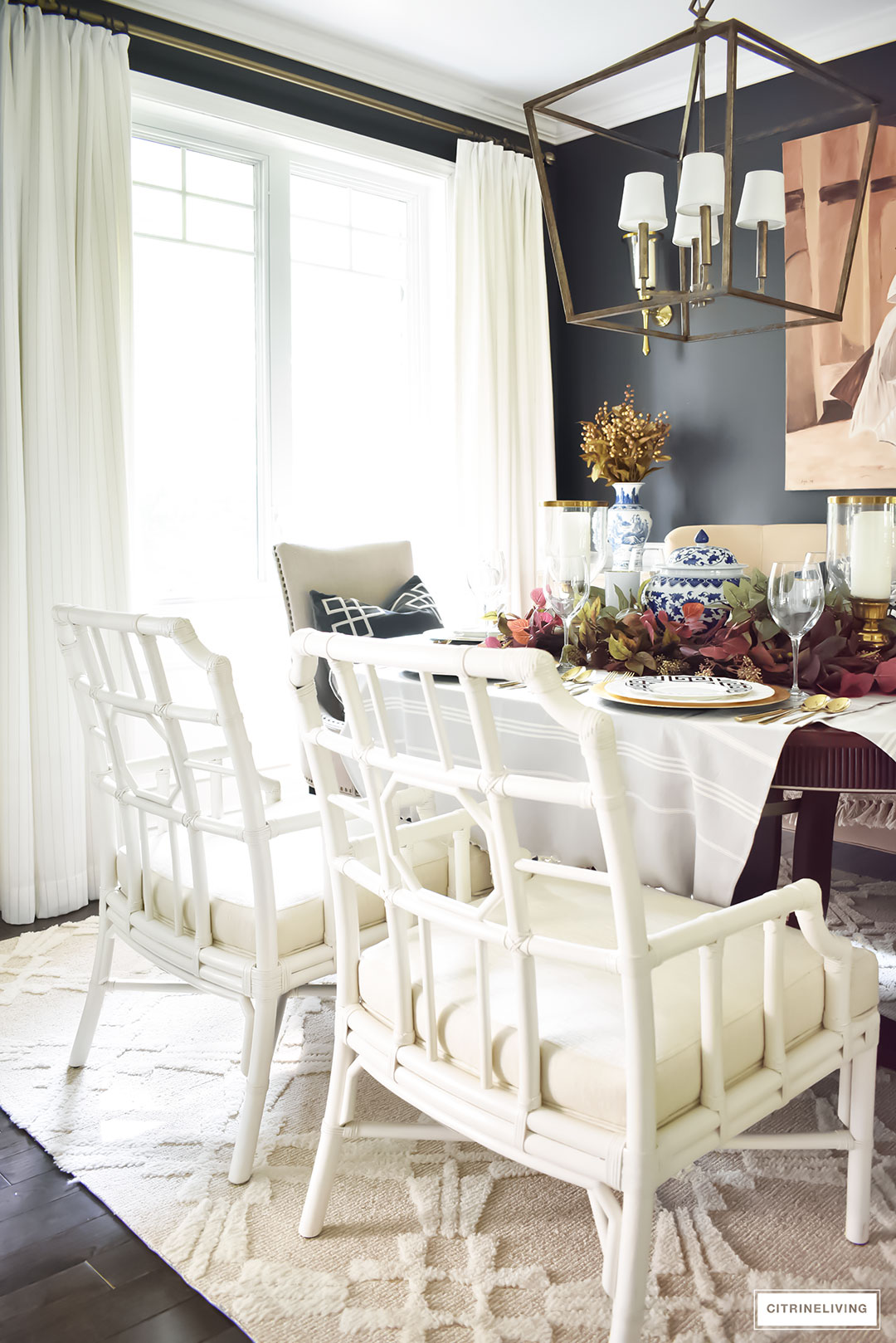 Dining room with black walls, white drapes, white lattice-back chairs, brass large scale chandelier. Fall tablescape with rich colors and blue and white accents.