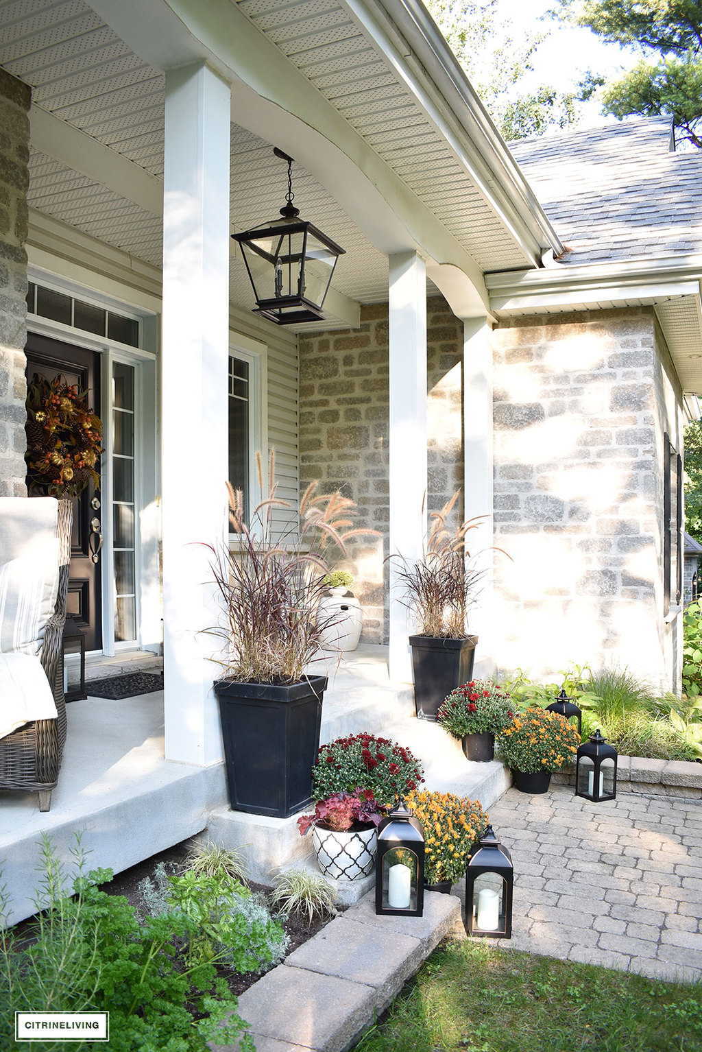 an elegant front porch decorated for fall