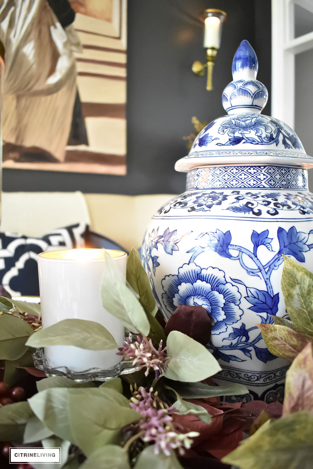 Create an elegant Fall tablescape using faux foliage in rich, autumnal hues, paired with gold, black and white tableware, and blue and white chinoiserie.