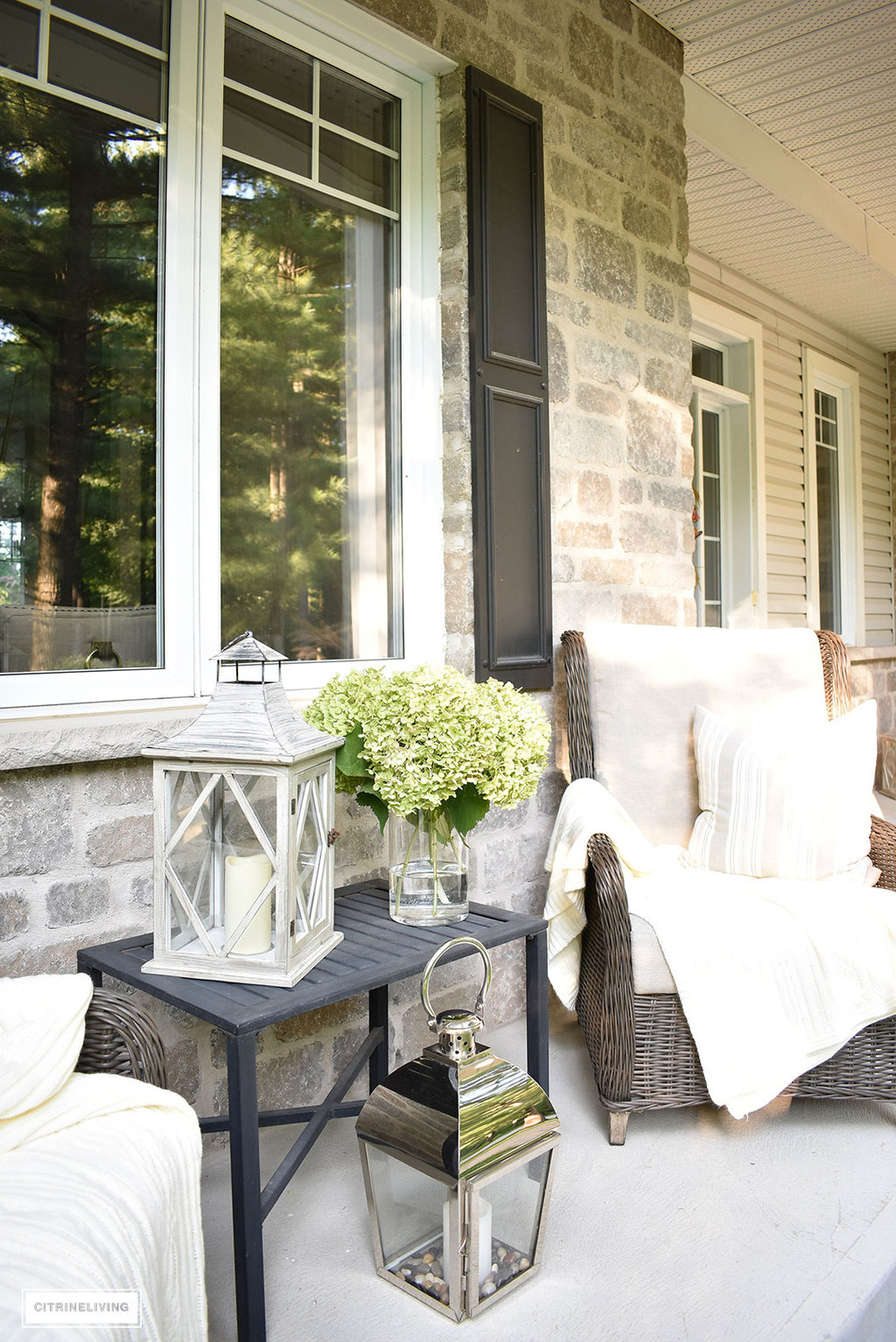 Create a cozy seating nook on your front porch this Fall, layered with blankets, fresh hydrangeas and lanterns.