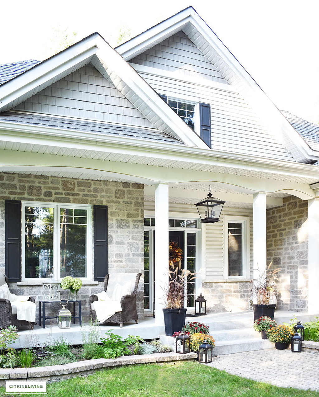 A simple and elegant front porch decorated for Fall with seasonal flowers in autumnal colors, and a sophisticated overscale wreath for the front door.