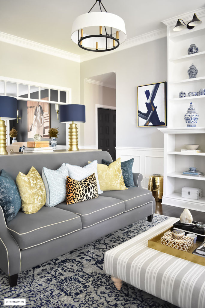 Fall Home Tour featuring this elegant living room with sophisticated navy and gold accents, drum shade chandeliers, gray sofas and blue and white accessories. Blue vintage style rug. Leopard pillow.