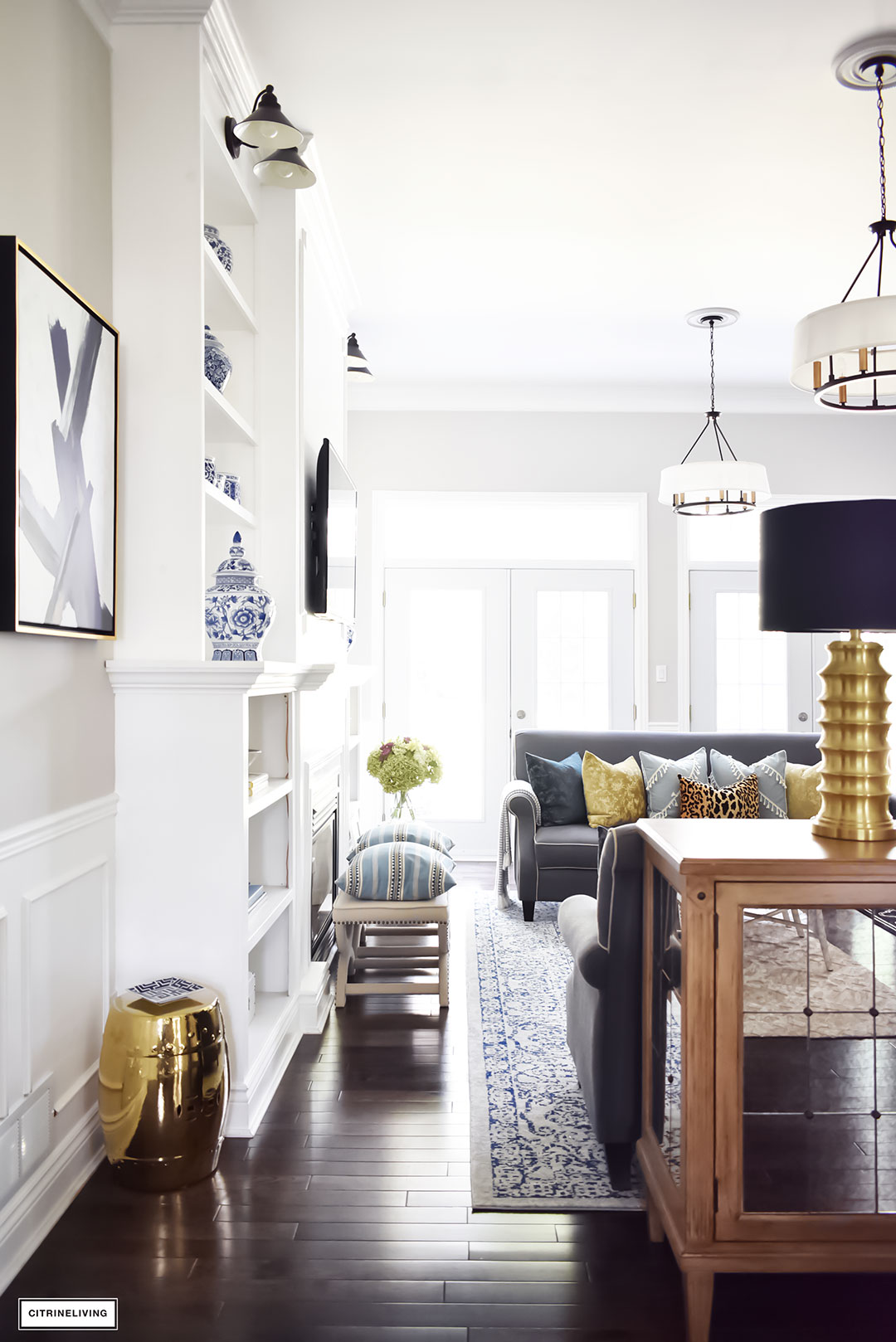 Fall Home Tour featuring this elegant living room with sophisticated navy and gold accents, drum shade chandeliers, gray sofas and blue and white accessories. Blue vintage style rug.