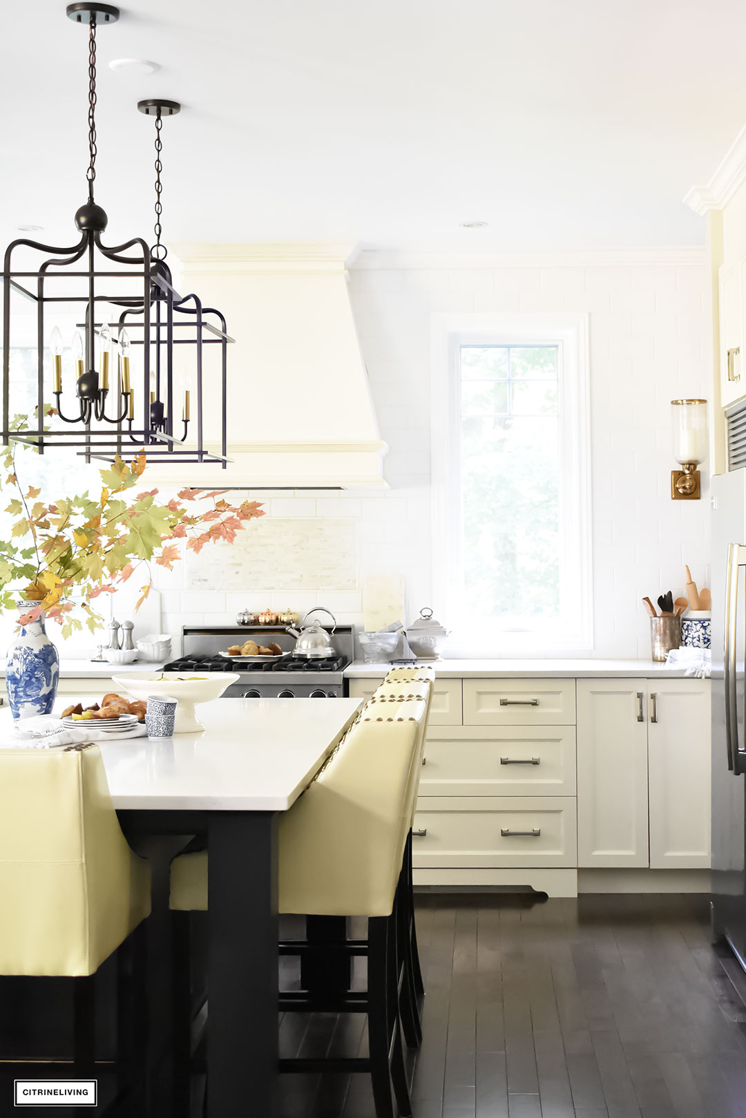 Fall Home Tour - casual elegant black and white kitchen with large black island and lantern style pendant lighting. Brass wall sconces.