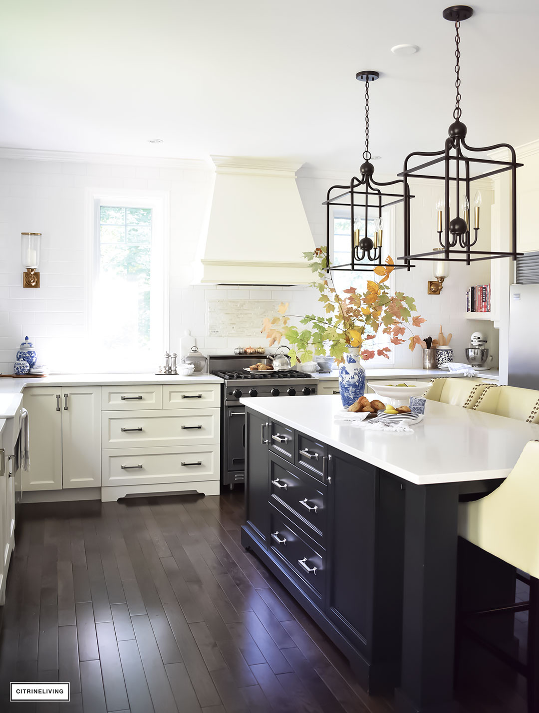 Fall Home Tour - casual elegant black and white kitchen with large black island and lantern style pendant lighting. Blue and white vases and Fall foliage.