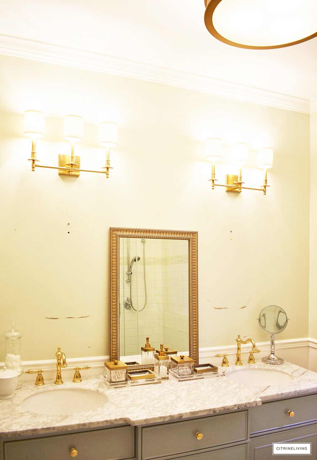 Gorgeous master bathroom makeover with wall panelling, brass lighting and a stunning gray vanity with marble counters.