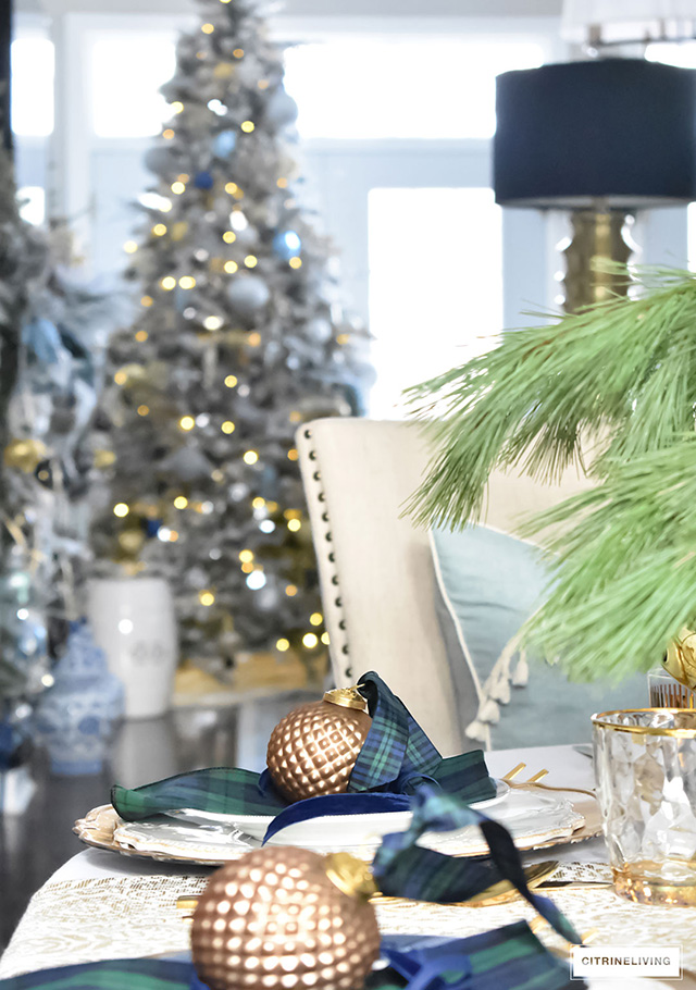 Gorgeous Christmas tablescape with classic navy and green tartan, accented with gold ornaments, chargers, flatware and glassware.