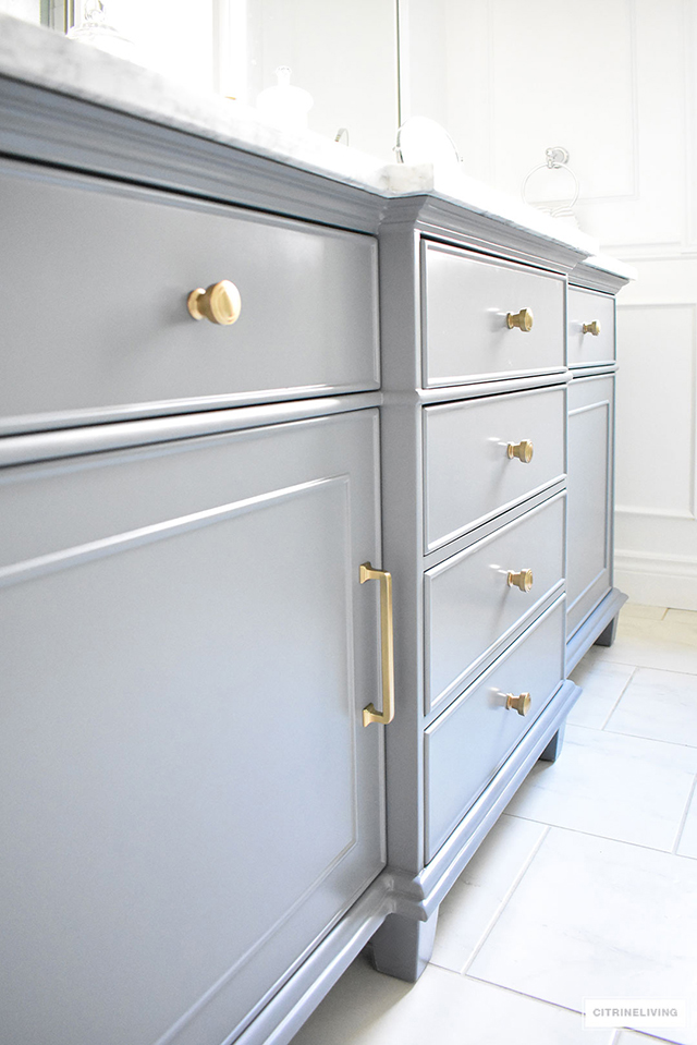Gorgeous grey, brass and white master bathroom featuring this standout vanity sure to make a statement in any bathroom!