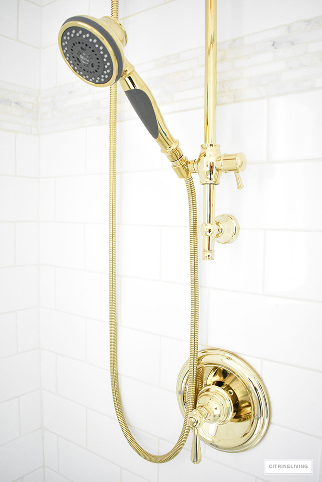 Gorgeous master bathroom makeover featuring brass handheld shower system