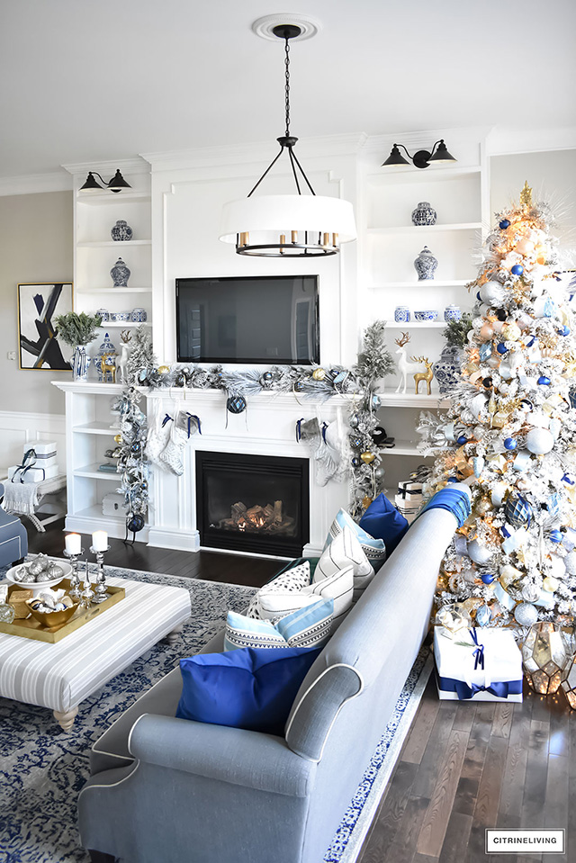 Christmas Home Tour - Gorgeous living room dressed in blues, gold, silver and flocked greenery is sophisticated,elegant and has an elevated look and feel.