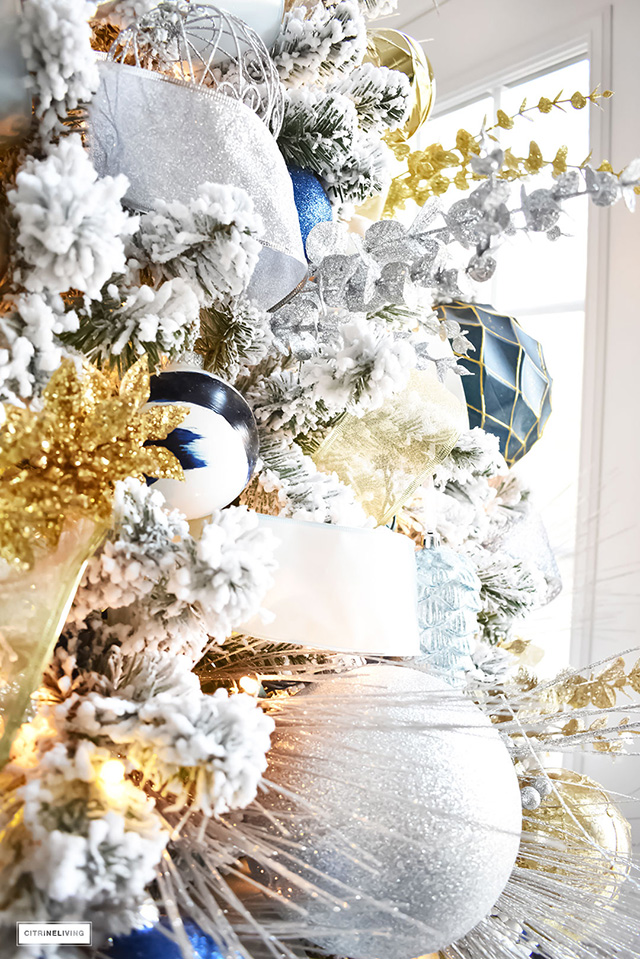 Beautiful, flocked Christmas tree adorned with navy, light blue and elegant metallics, is sophisticated and refreshing for your holiday decor.