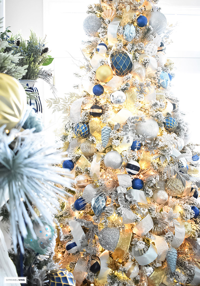 beautiful flocked christmas tree adorned with navy light blue and elegant metallics - Blue And Gold Christmas Decorations
