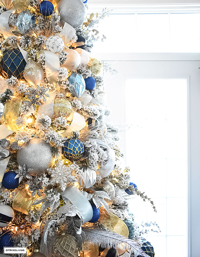 beautiful flocked christmas tree adorned with navy light blue and elegant metallics is - Christmas Tree Blue