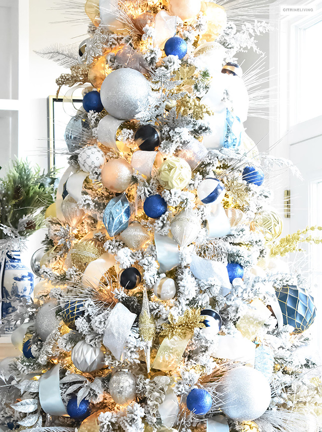beautiful flocked christmas tree adorned with navy light blue and elegant metallics is - Silver And Blue Christmas Tree