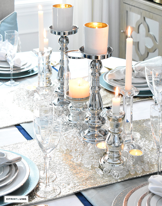Create a simple and elegant NewYear's tablescape using classic white and silver china, gold sequin runners and light blue accents.