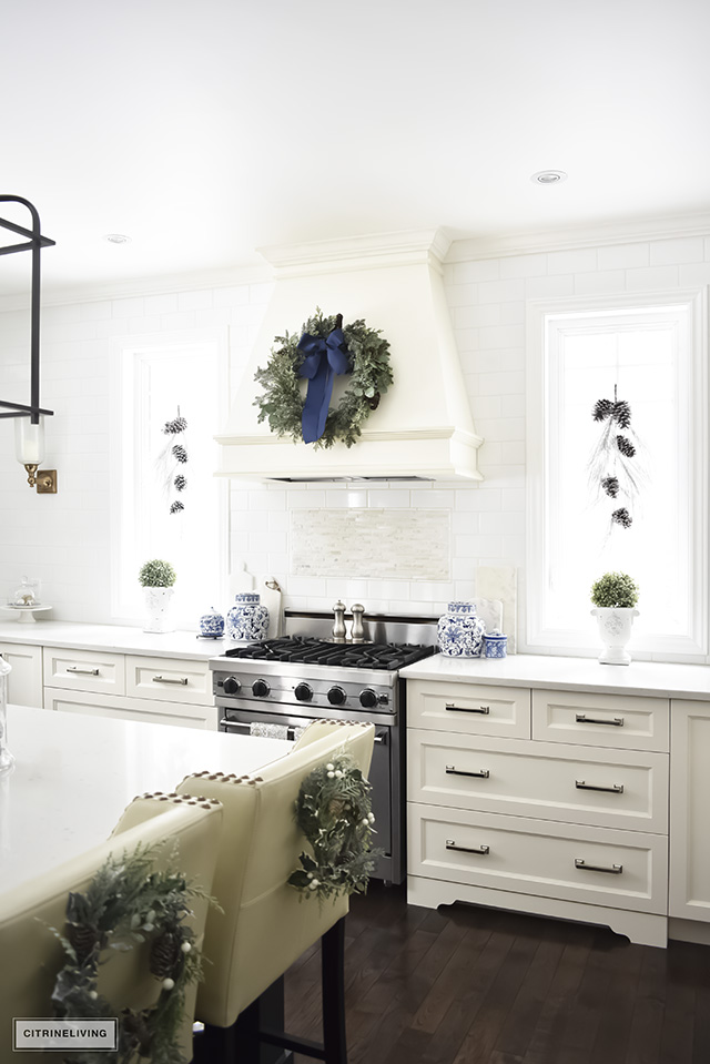 A beautiful Christmas kitchen with blue and white chinoiserie, paired with holiday greenery for a sophisticated, festive and elegant look.