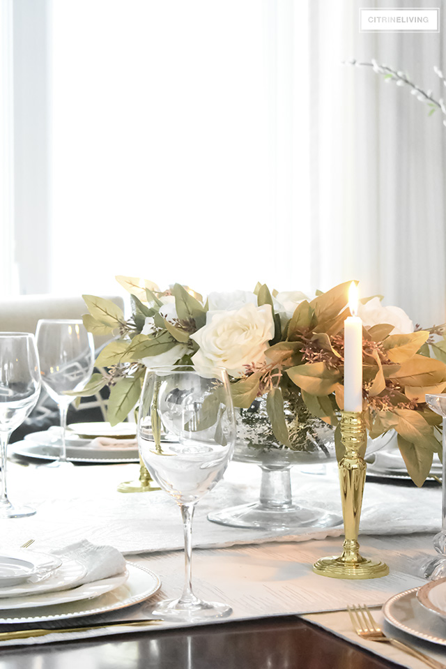A gorgeous neutral Valentine's table with tones of white layered with metallic accents and a beautiful white rose centrepiece.