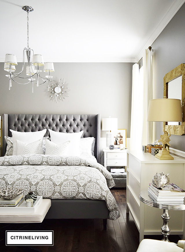 Beautiful master bedroom featuring upholstered headboard with nailhead trim and grey and white medallion print bedding. Ralph Lauren Washboard wall color.