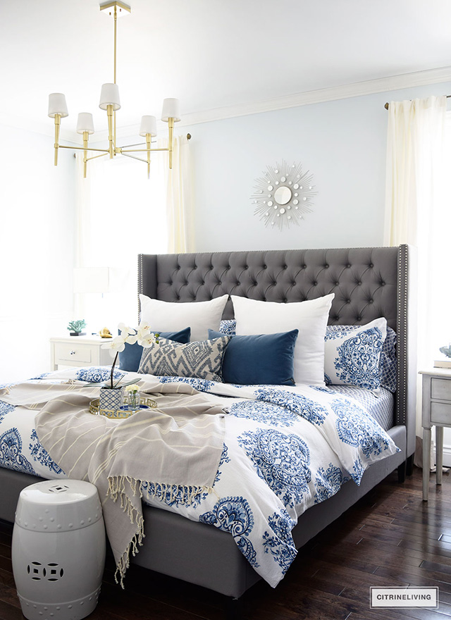 grey-upholstered-bed-with-blue-and-white-bedding