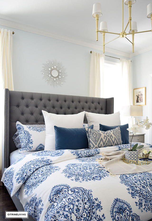 Grey Upholstered Bed With Blue And White Bedding