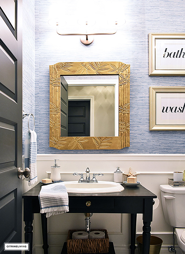 Beautiful bathroom with blue grasscloth wallpaper, black vanity and gold painted mirror makes this space classic and chic.