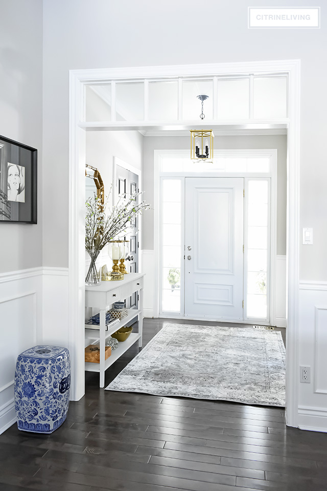 A light and bright entryway makeover that was super simple to achieve! Some chalk paint, a new mirror and new rug have completely transformed this foyer!