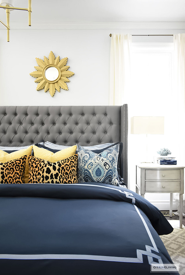 navy-bedding-grey-upholstered-heaboard-blue-and-white-pillows-gold-accents