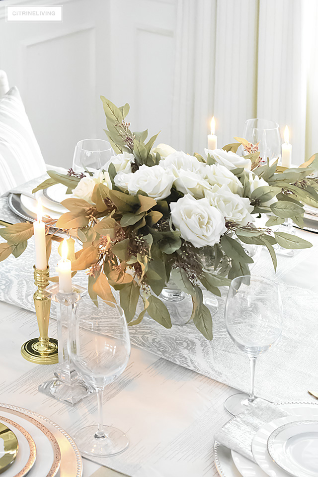 Faux florals compliment silver and white china paired with brass flatware for a beautiful neutral tablescape.