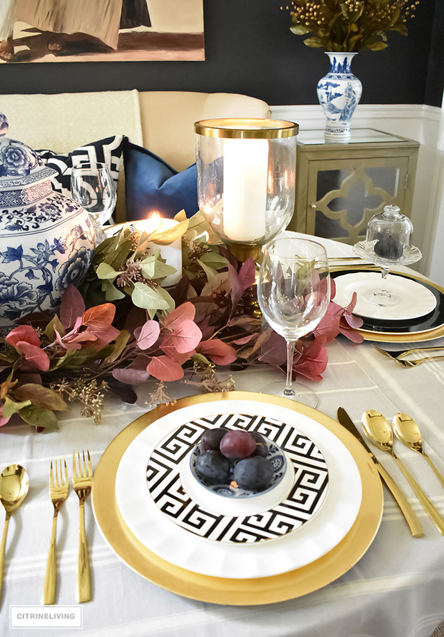 Beautiful table with black and white greek key dishes with gold chargers and brass flatware