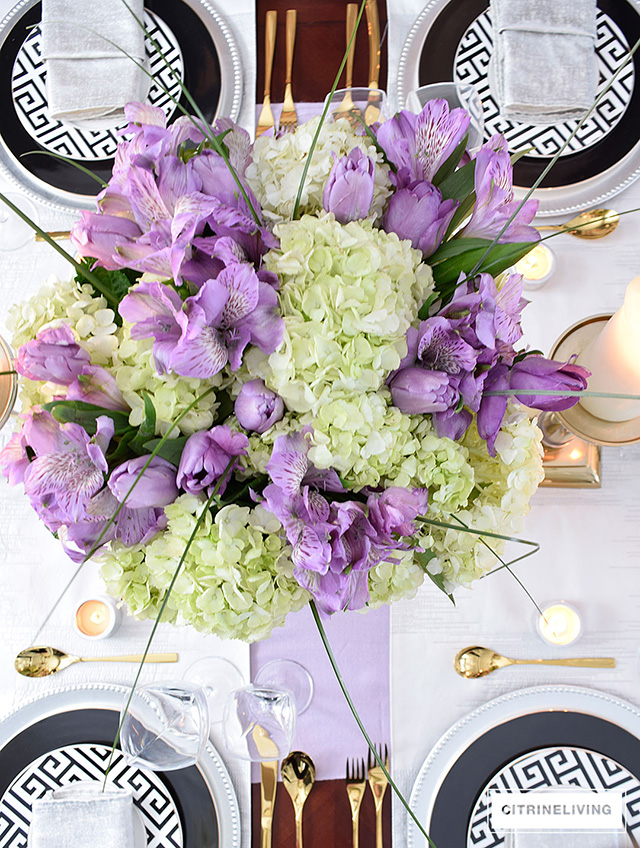 Black and white greek key plates paired with gold, silver and lavender is a stunning combination for any table!  White ydrangeas, with lavender flowers softens the look and adds a feminine touch.