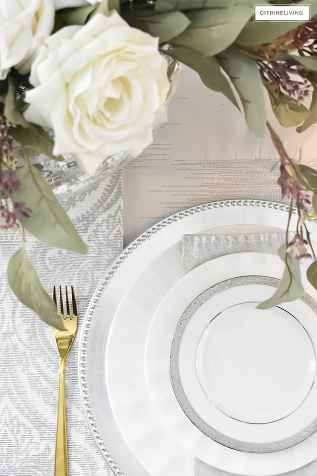 Faux roses compliment silver and white china paired with brass flatware for a beautiful neutral tablescape.