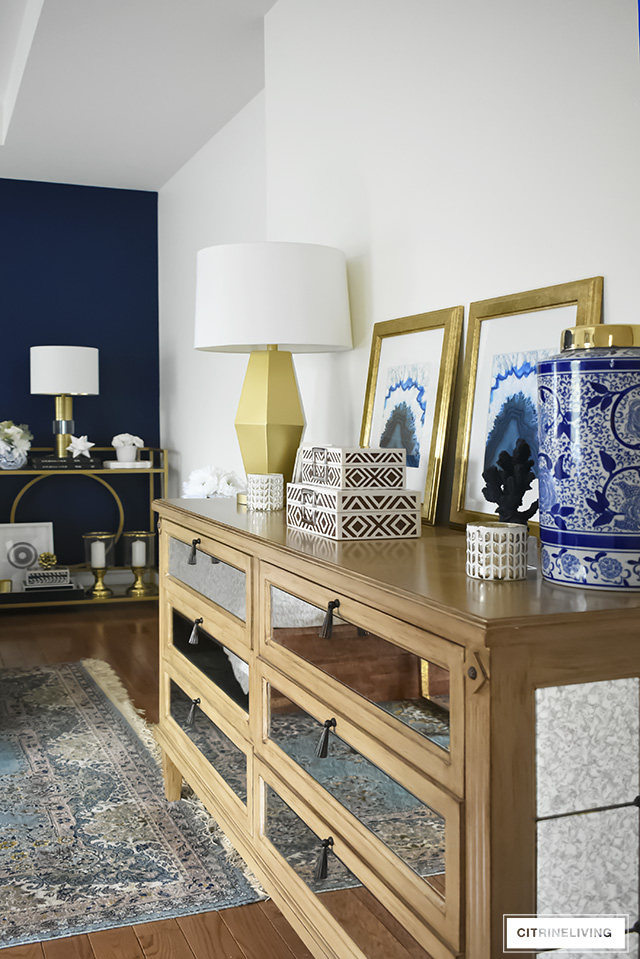 Antique mirrored dresser styled with brass and blue and white accessories.