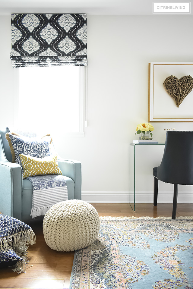 A gorgeous reading nook with layers of blues - vintage rug, eclectic pillows, graphic roman blind all layered together create the perfect boho-glam bedroom.