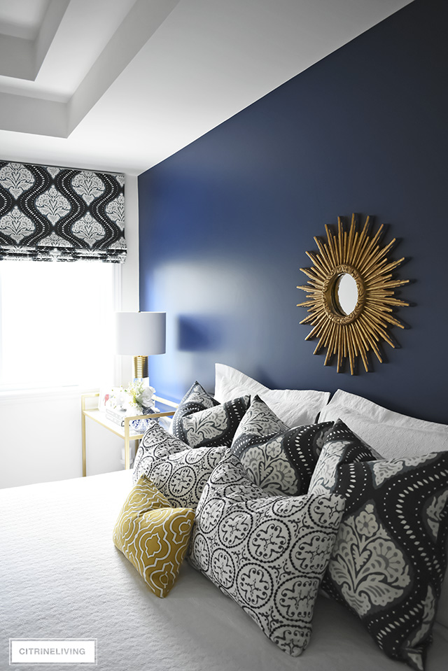 Robert Allen custom pillows and roman blind layered together for an eclectic boho-glam look, accented with a classic brass sunburst mirror.